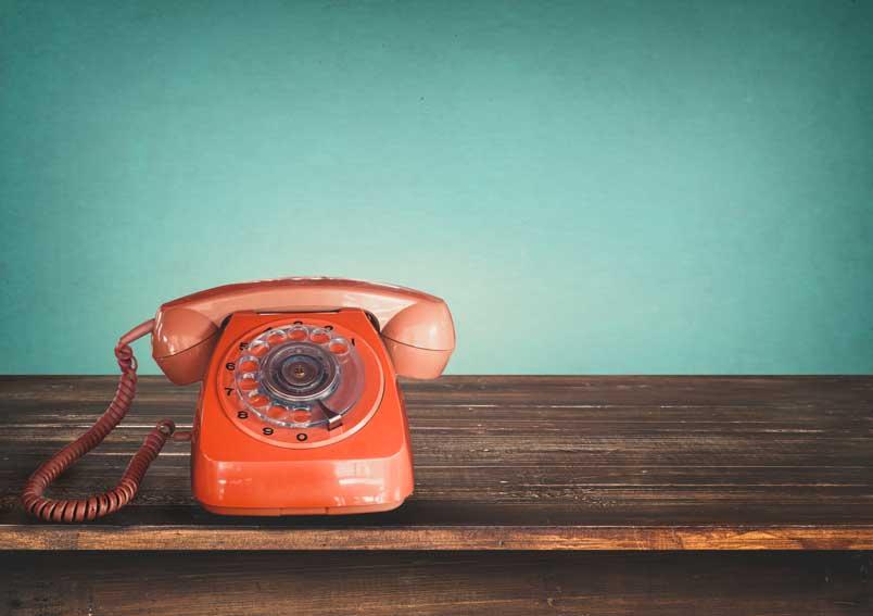 En rød telefon på en brun benk